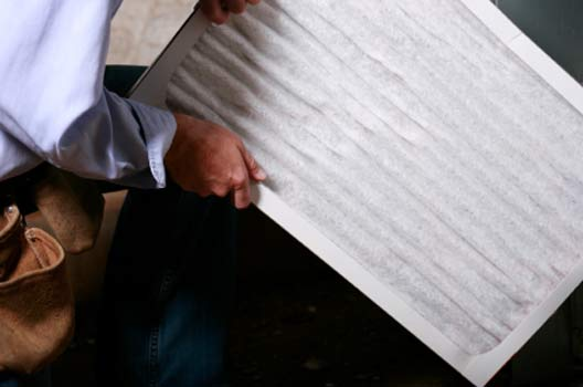 HVAC Tech replacing pleated air filter